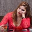 Depressed young woman drinking and smoking - Stock Photo