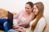 Two beautiful teenage girls surfing the internet with notebook — Zdjęcie stockowe