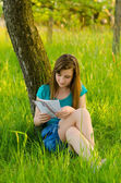 Beautiful teenage girl reading letter while sitting under the tree on sunny spring day — Stock Photo