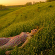 Beautiful happy girl lying on the green meadow during spring sunrise — Stock Photo
