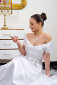 Beautiful bride in wedding dress sitting on the floor and looking at her wedding ring — Stock Photo