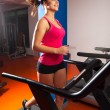 Beautiful smiling girl running on treadmill in the gym — Stok fotoğraf