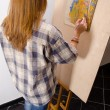 Young female painter painting landscape in her art studio — Stock Photo