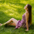 Beautiful young girl sitting on the meadow on sunny summer day — Stock Photo
