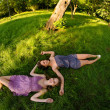 Two beautiful girls lying on the grass in the park on sunny summer day — Stock Photo