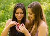 Smiling girls sharing strawberries outdoor — Stockfoto