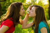 Teenage girls smelling flowers in orchard — Stock Photo