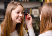 Happy teenage girl putting make up — Foto de Stock