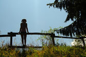 Silhouette of girl standing on the wooden fence — Stock Photo