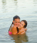 Two teenage girls hugging in the river — Stock Photo
