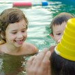 Father and his children playing in the swimming pool — Stock Photo #29381471