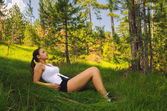 Beautiful girl resting in the forest — Stock Photo