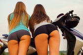 Sexy girls seen from behind leaning on scooter — Stock Photo