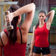 Girl exercising in the gym with dumbbells — Stock Photo #30407779