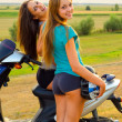 Two beautiful girls resting after riding scooter — Stock Photo #30771149