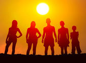 Silhouettes of boys and girls on the beach — Stock Photo