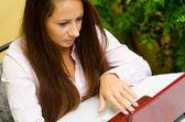 Chica que trabaja en el cuaderno en casa — Foto de Stock
