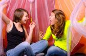 Two teenage girls having fun on the bed — Stock Photo