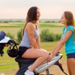 Stock Photo: Two beautiful girls resting after riding scooter