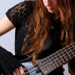 Beautiful girl playing bass guitar — Stock Photo #33179185