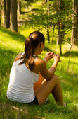 Beautiful girl sitting on grass in the forest — Stock Photo