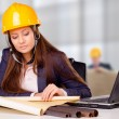 Young female architect studying plans — Stock Photo