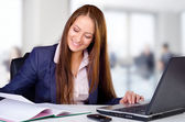 Smiling business woman in her office — Stock Photo