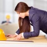 Young female architect studying plans — Stock Photo