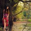 Beautiful woman standing by the tree — Stockfoto