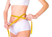 Young fit female measuring waist — Stock Photo