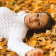 Beautiful girl lying on the autumn leaves — Stock Photo