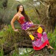 Lady in long dress sitting on the tree trunk — Stockfoto