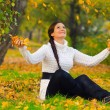 Girl throwing dry autumn leaves in the air — Stock Photo