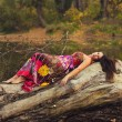 Beautiful girl lying on the tree trunk — Stock Photo