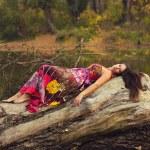 Beautiful girl lying on the tree trunk — Stock Photo #37447257