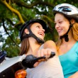 Stock Photo: Two teenage girlfriends riding scooter