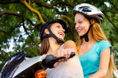 Two teenage girlfriends riding scooter — Stock Photo