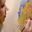 Young female artist painting landscape — Stock Photo
