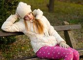 Chica triste sentado en el banquillo — Foto de Stock