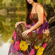 Beautiful lady in long dress sitting on the tree — Stock Photo