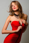 Fashion beauty unzipping red dress — Stock Photo