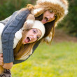 Happy teenage girls piggyback riding in the nature — Stock Photo #39664385