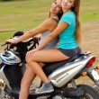 Two beautiful girls enjoying motorcycle ride at countryside — Stock Photo