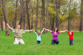 Young family having fun in the forest — Stock Photo