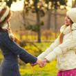 Two beautiful girls holding hands in the park — Stock Photo