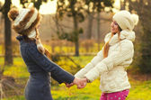 Two beautiful girls holding hands in the park — Стоковое фото