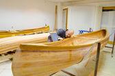 Young carpenter examining new canoe — Foto de Stock