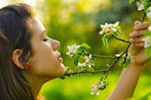 Girl smelling flowers in the orchard — Stock Photo