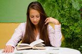 Beautiful girl reading book in the garden — Stock Photo