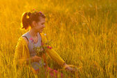 Smiling girl picking flowers on the meadow — Stock Photo